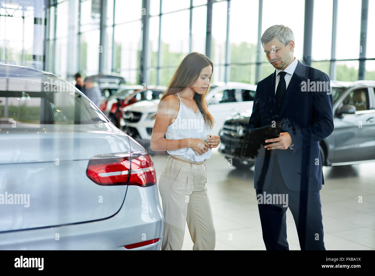 Young female customer asking mature sales manager to help in car dealership. - Stock Image