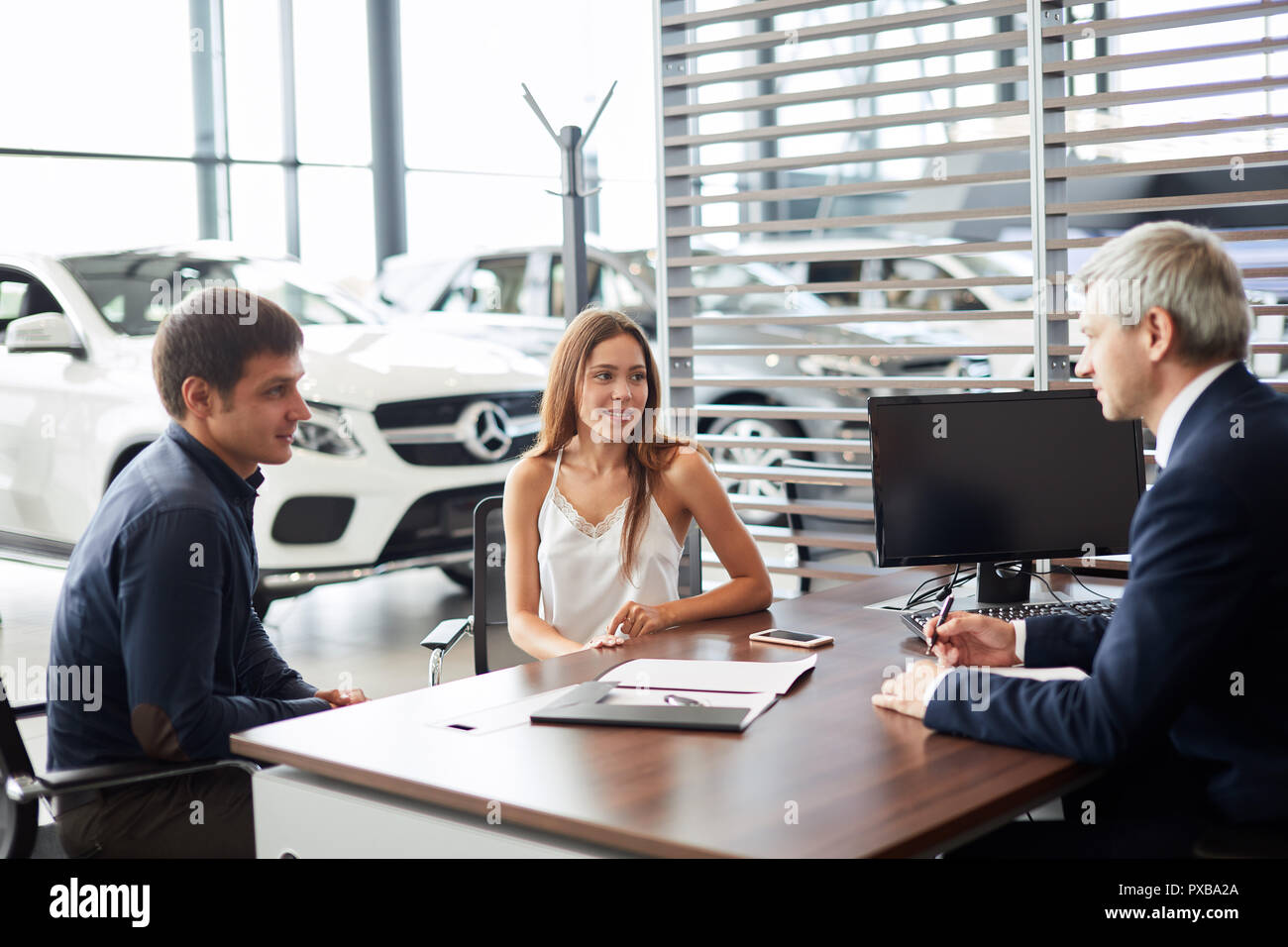 Mature sales manager signing contract with clients at car dealership office - Stock Image