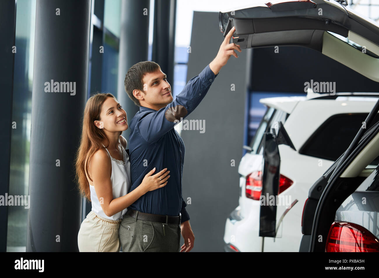 Loving smart couple choosing a car at the car dealership showroom - Stock Image