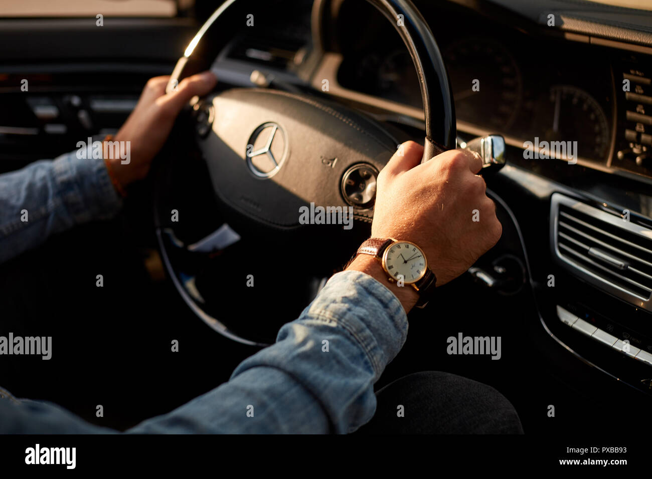 male's arms on the steering wheel Stock Photo
