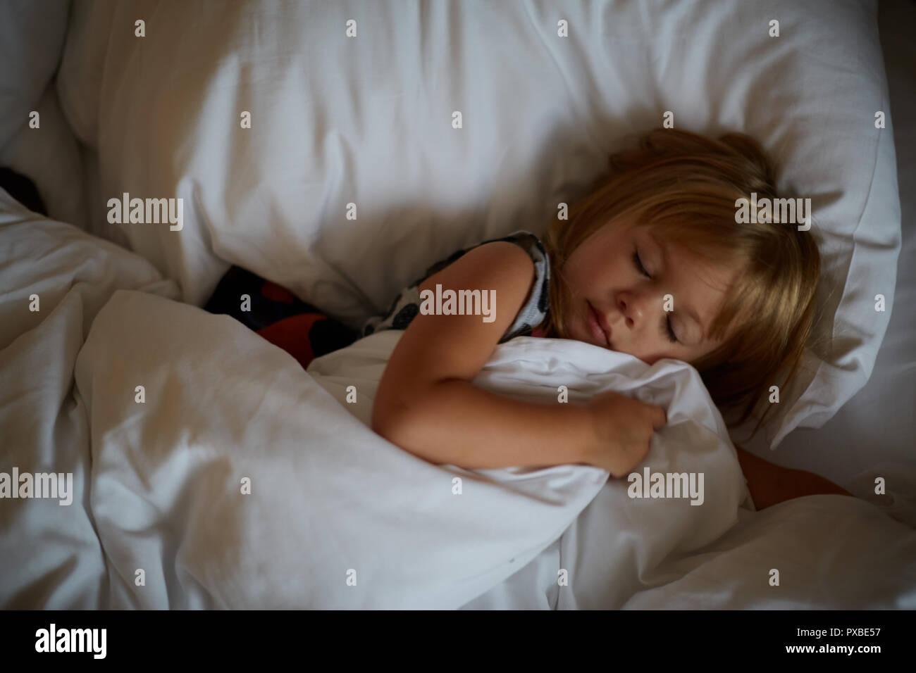 Girl lying in bed after sleeping. morning awakening, a fun morning, playing in bed - Stock Image