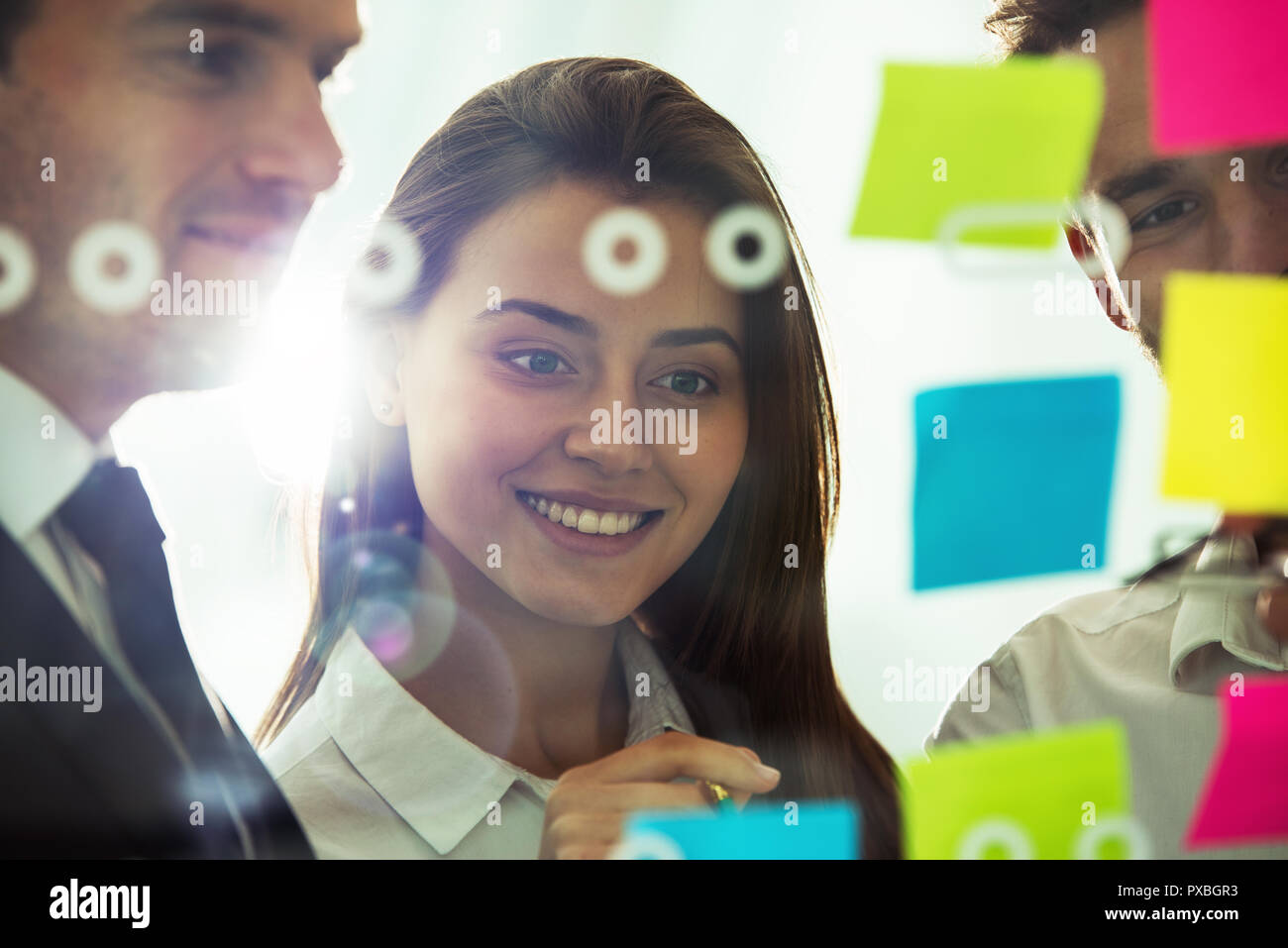 Happy girl works with colleagues in office with post it notes in foreground. Concept of teamwork and partnership - Stock Image