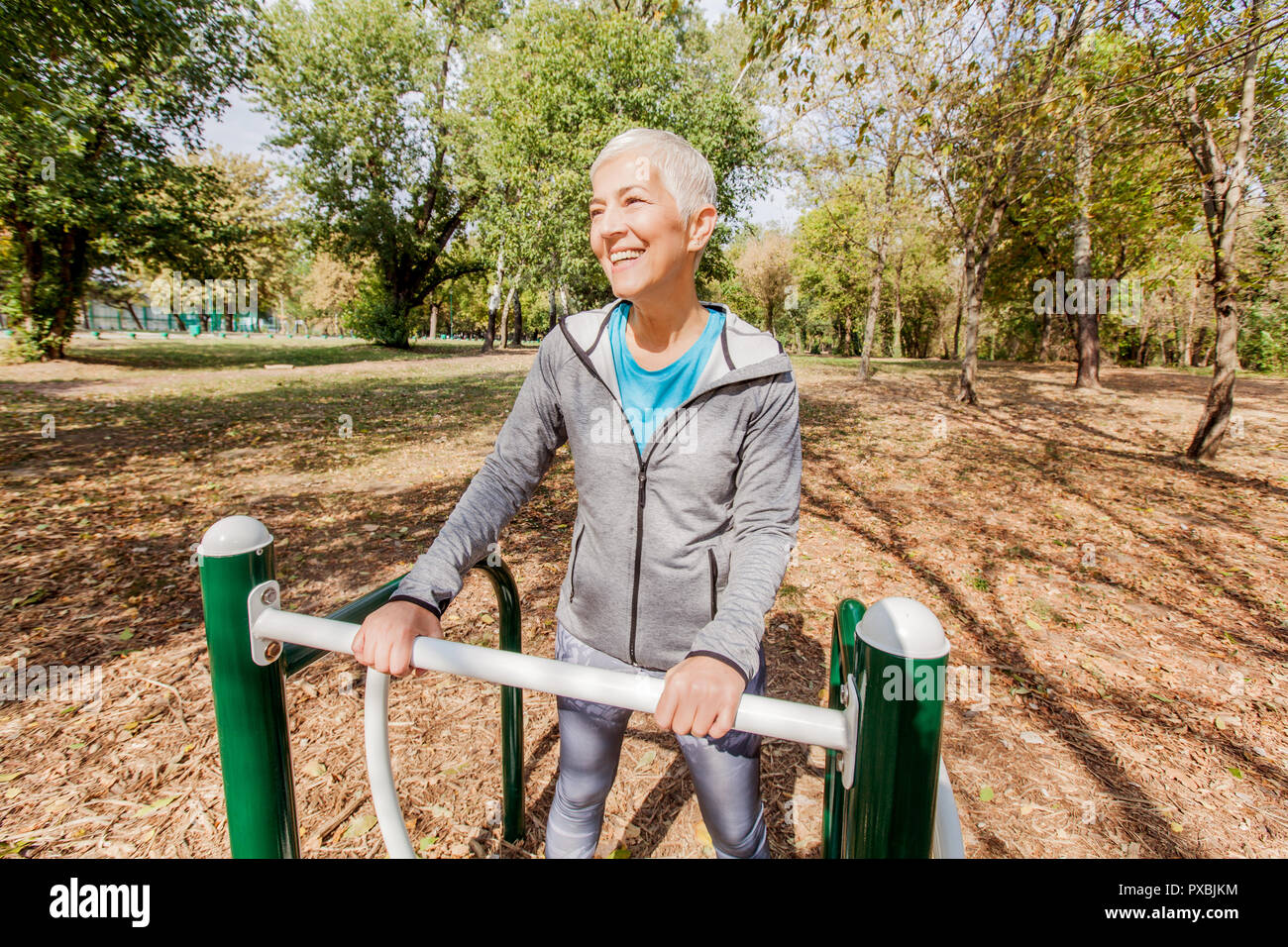 Elderly Woman In Sports Clothes Exercising At Outdoor Fitness Park, Healthy Lifestyle Mature People. Stock Photo