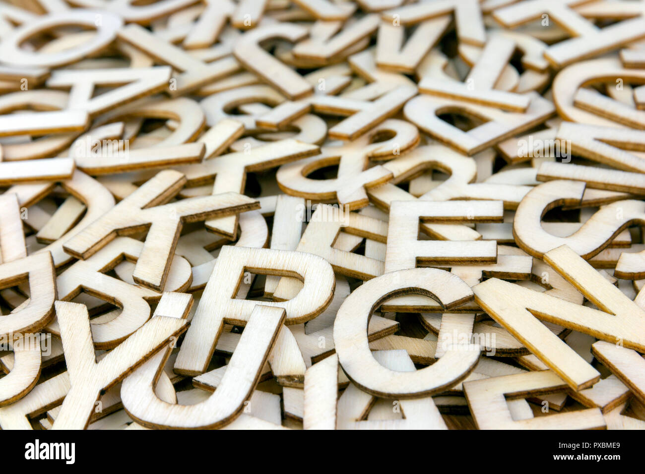 Pile of mixed wooden capital letters close up with a shallow depth of field - Stock Image
