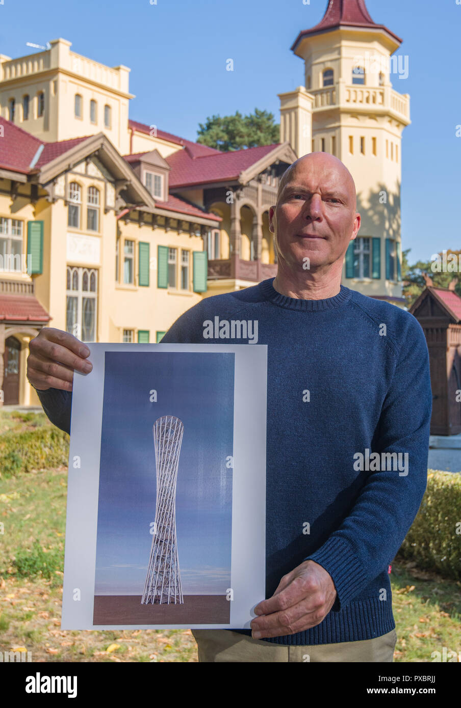 Storkow, Germany. 11th Oct, 2018. Rainer Opolka, entrepreneur and artist of the company Zweibrüder Kunst- und Kultur GmbH, stands in front of his castle Hubertushöhe and shows a design of an observation tower. Rainer Opolka wants to develop the area around Hubertushöhe Castle into an art and literature park. (to dpa-KORR 'From elitist castle hotel to art and literature park for all' from 21.10.2018) Credit: Patrick Pleul/ZB/dpa/Alamy Live News - Stock Image