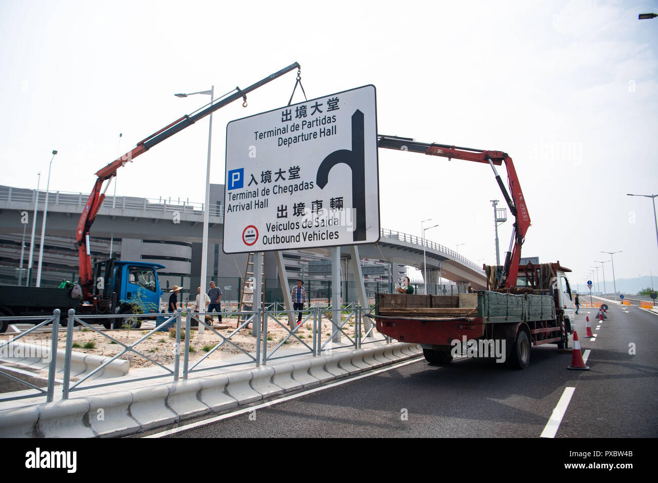 Macao, China. 19th Oct, 2018. Workers install facilities on the artificial island for the Hong Kong-Zhuhai-Macao Bridge in Macao, south China, Oct. 19, 2018. The bridge will start operation on Oct. 24, further integrating cities in the Pearl River Delta. Credit: Cheong Kam Ka/Xinhua/Alamy Live News - Stock Image