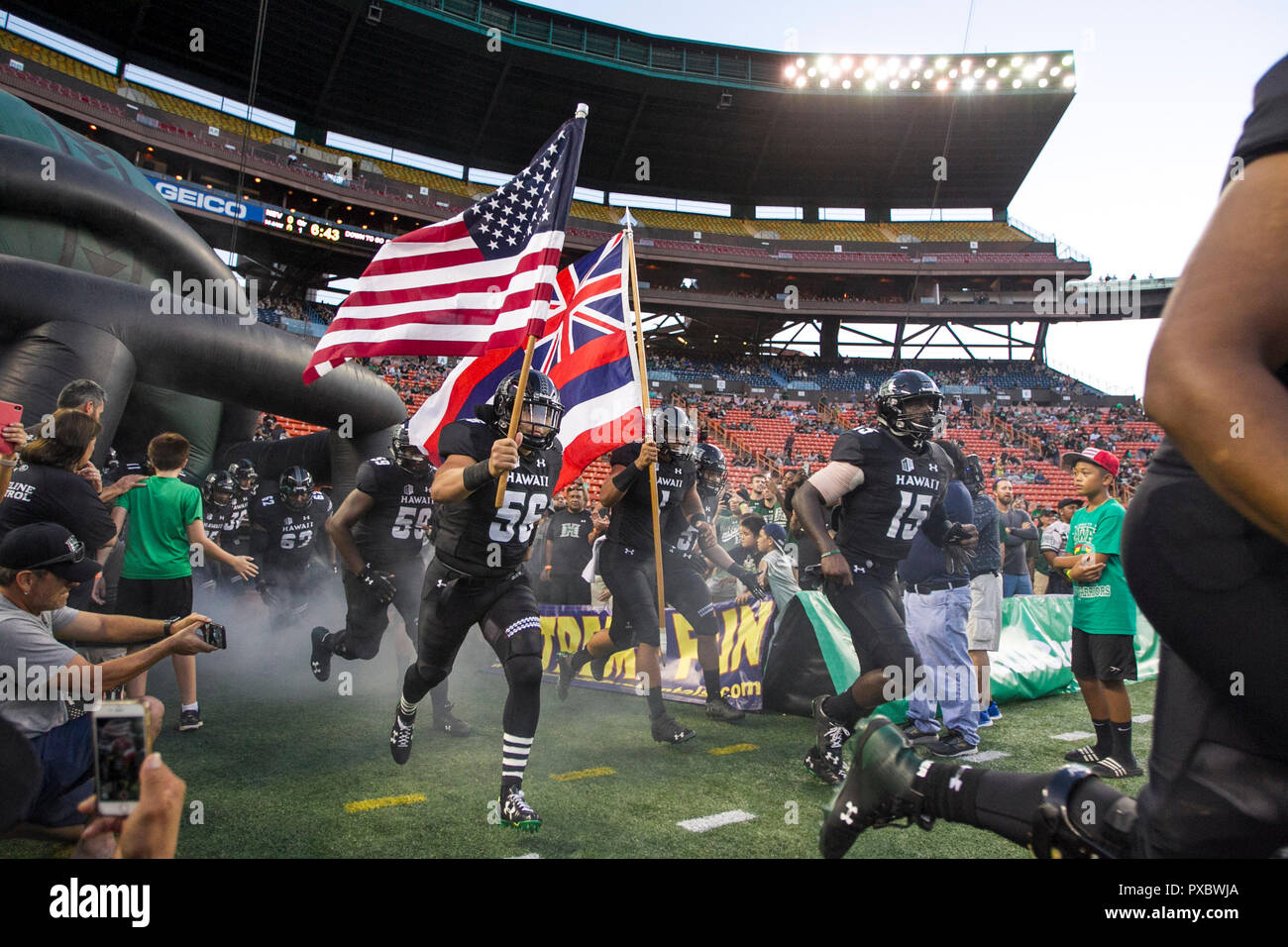 October 20, 2018 - Hawaii players carry the flags of USA and Hawaii before the game between the Hawaii Rainbow Warriors and the Nevada Wolfpack at Aloha Stadium in Honolulu, HI. - Glenn Yoza/CSM Stock Photo