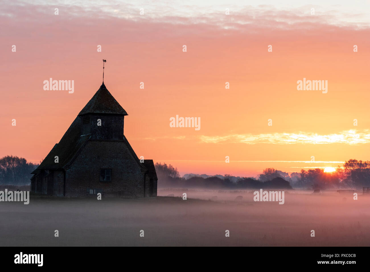 Sunrise and orange cloudy sky over the lonely Thomas a Becket church at Fairfield on Romney Marsh. Fields covered in mist, laying the landscape. Some sheep and cows in the mist. Stock Photo