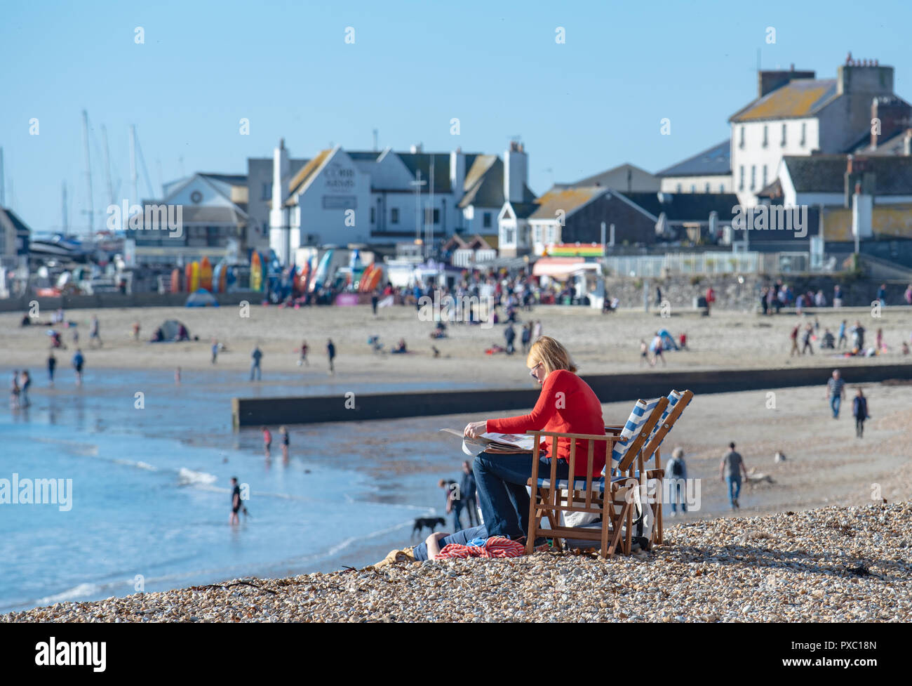 Lyme Regis, Dorset, UK. 21st October 2018.  UK Weather:  Warm weekend sunshine and clear blue skies at Lyme Regis. A woman sits in a deckchair reading a newspaper in Lyme Regis as Britain enjoys one last sunny weekend before chillier, wintery conditions arrive and temperatures plummet later in the week. Credit: Celia McMahon/Alamy Live News - Stock Image