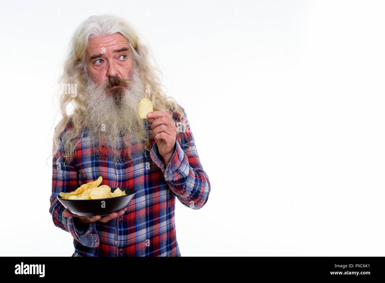 Studio shot of senior bearded man thinking while eating bowl of  - Stock Image