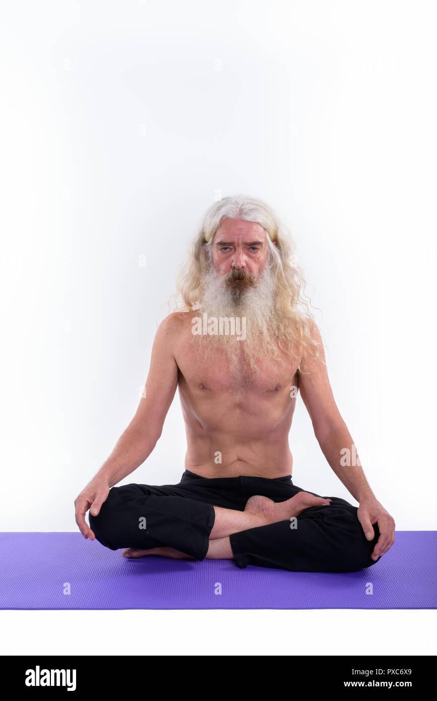 Senior bearded guru man sitting on yoga mat with legs crossed - Stock Image