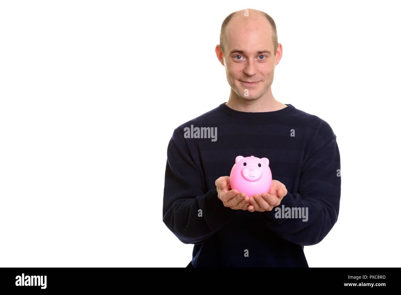Bald Caucasian man holding piggy bank and looking at camera - Stock Image