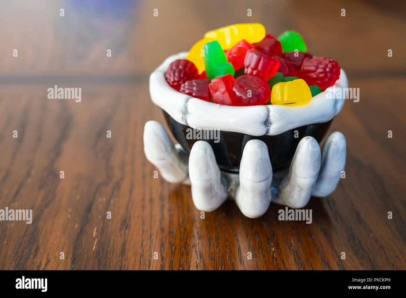 Skeleton hand with bowl of Candy during halloween - Stock Image