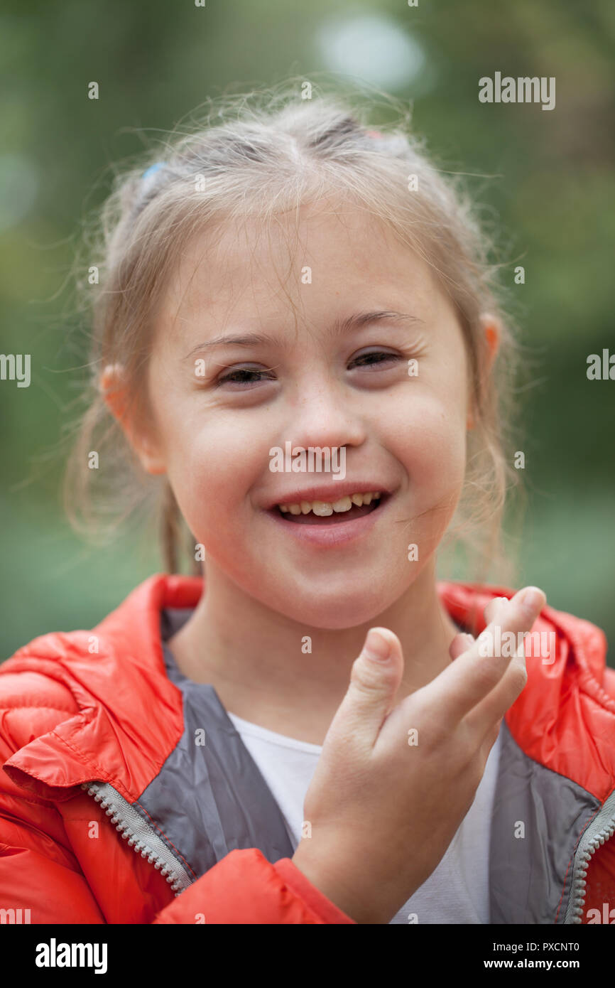 Portrait of a girl with special needs close-up on a background of foliage - Stock Image