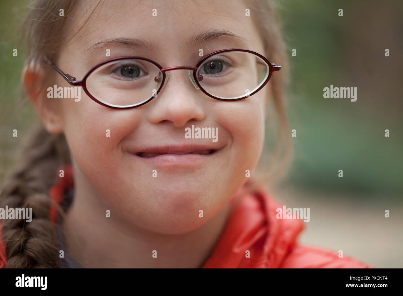 Portrait of a girl with special needs in glasses close-up in nature - Stock Image