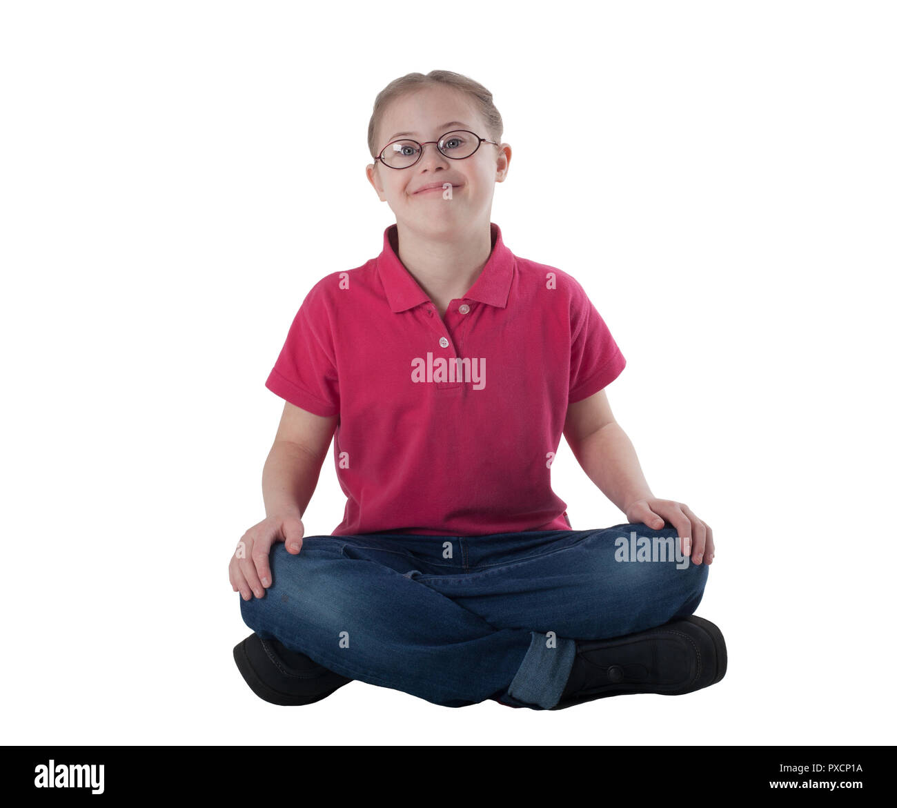 Portrait of a girl in glasses sitting cross-legged on a white background - Stock Image
