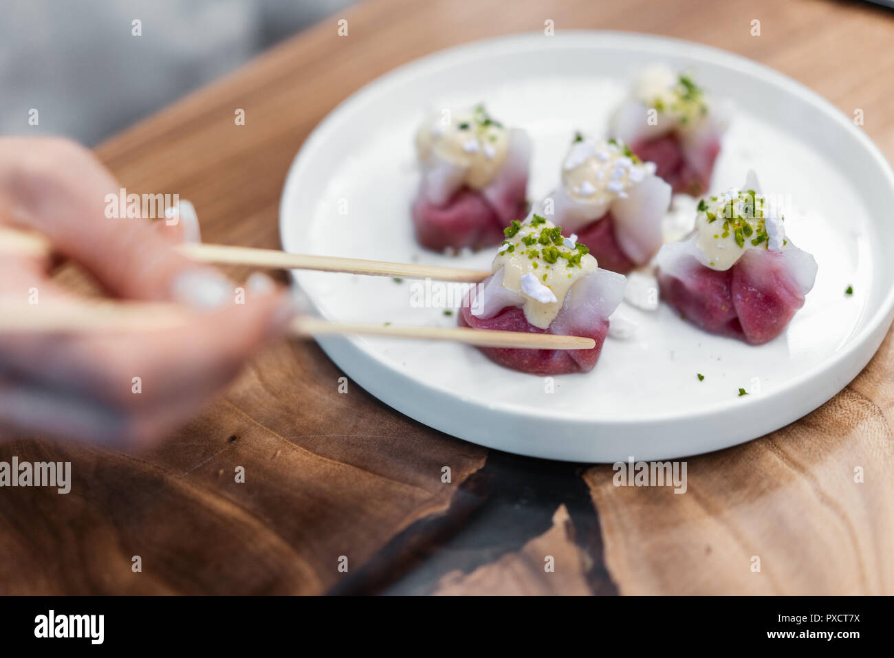 Chinese and korean dumplings on the white plate decorated with pistachio. - Stock Image
