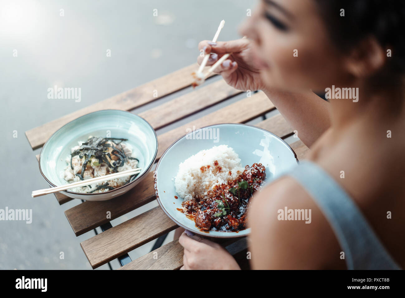 Beautiful woman eating chicken with rice in street cafe of chinese food. - Stock Image