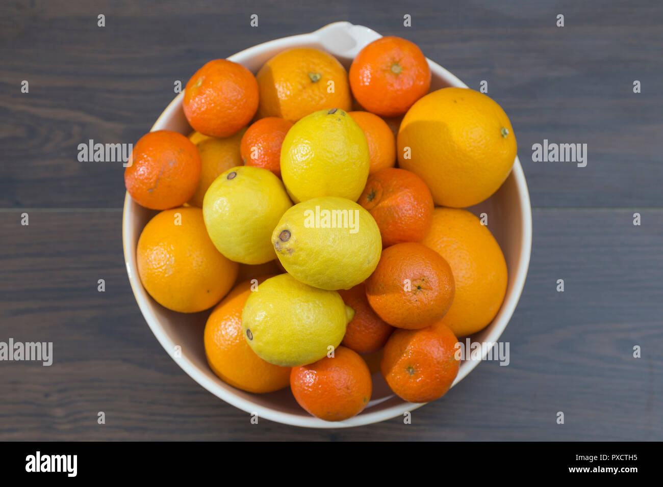 top view of a fruit bowl with oranges, tangerines and lemons, Mediterranean citrus, on a dark background in brown tones - Stock Image