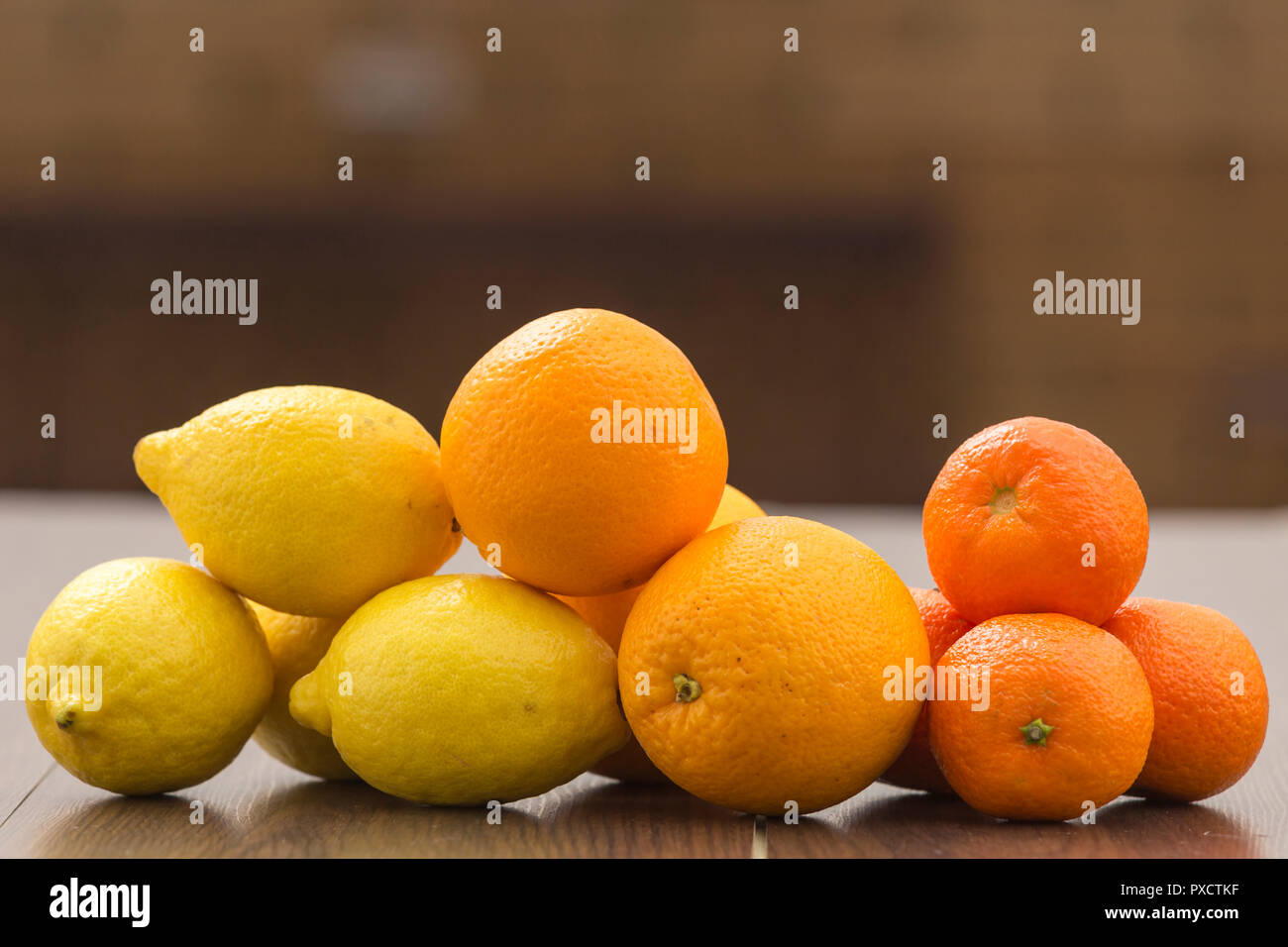 still life with oranges, lemons and tangerines placed together in groups, on a background and surface of brown tones - Stock Image