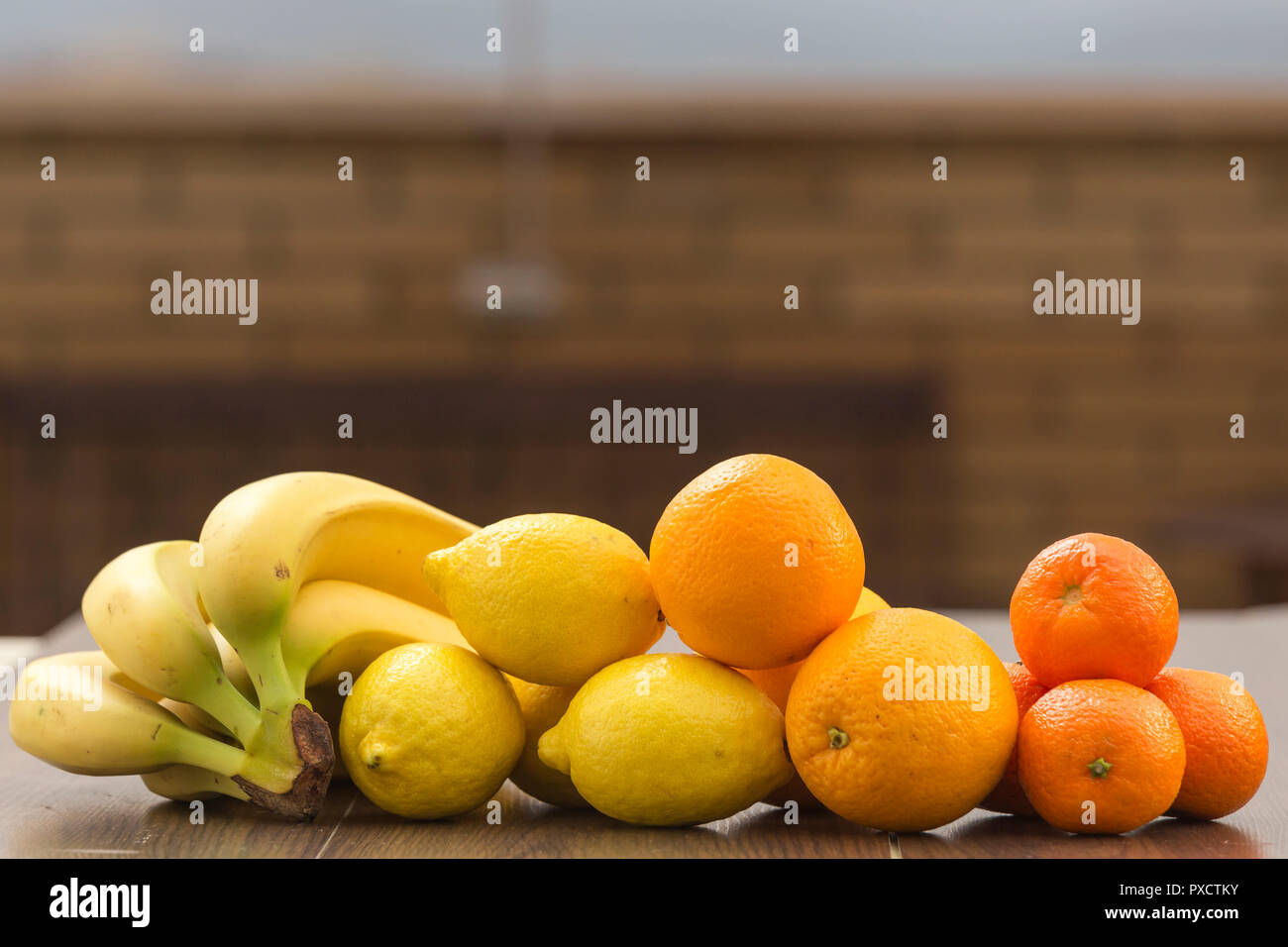 Still life with oranges, lemons, bananas and tangerines placed together in groups, on a background and surface of brown tones - Stock Image