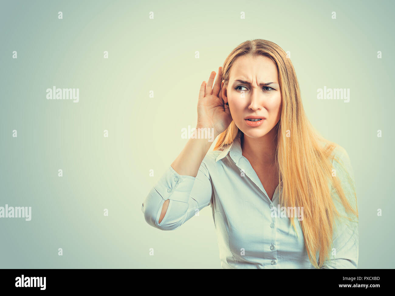 Blond woman in white shirt frowning while trying to listen to gossips on gray background - Stock Image
