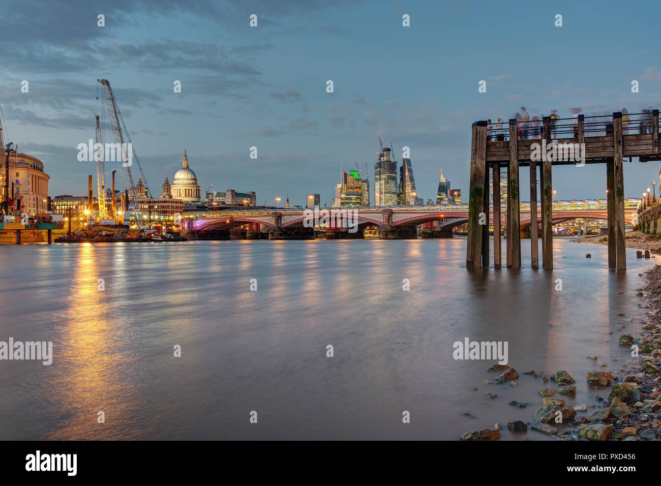 An old pier, the St Pauls cathedral, Blackfriars Bridge and the City of London at dusk - Stock Image