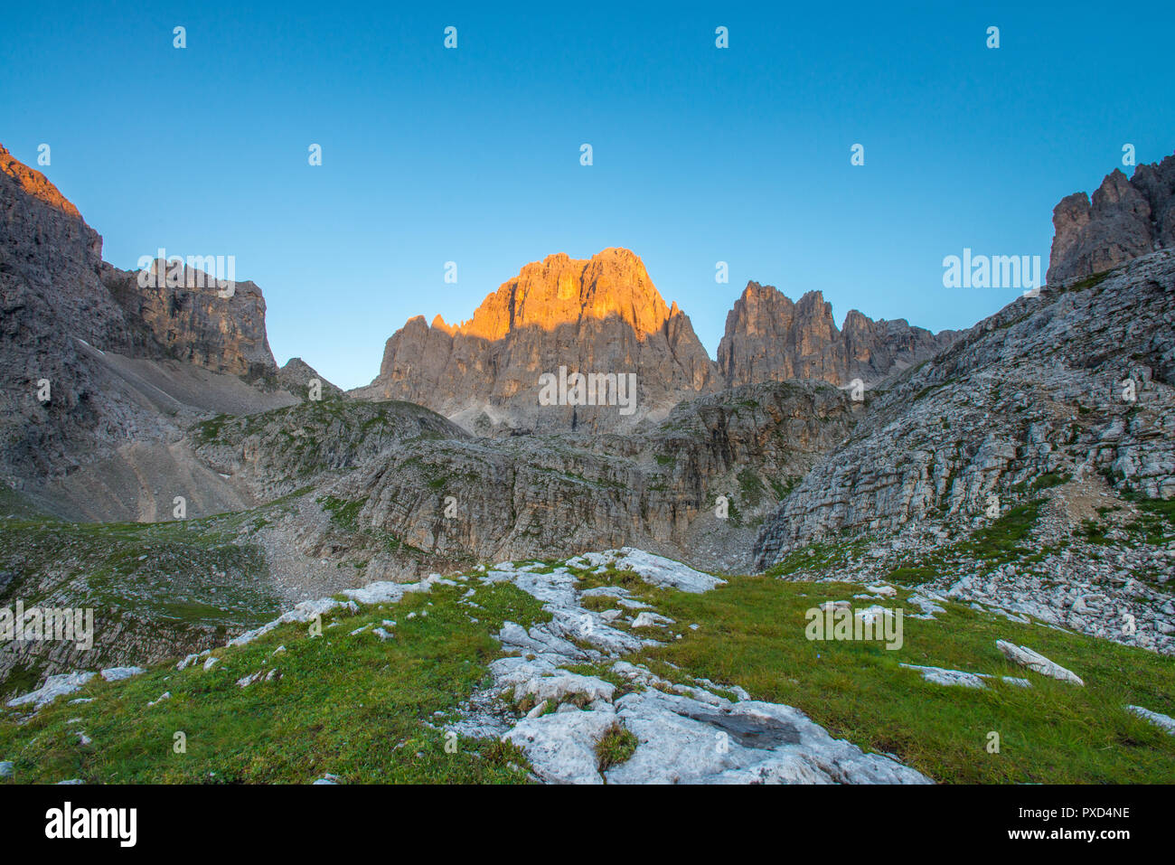 First daylight in the mountains, glowing mountain wall in the sunrise. Grass, rocks and boulders. Cloudless blue sky. - Stock Image