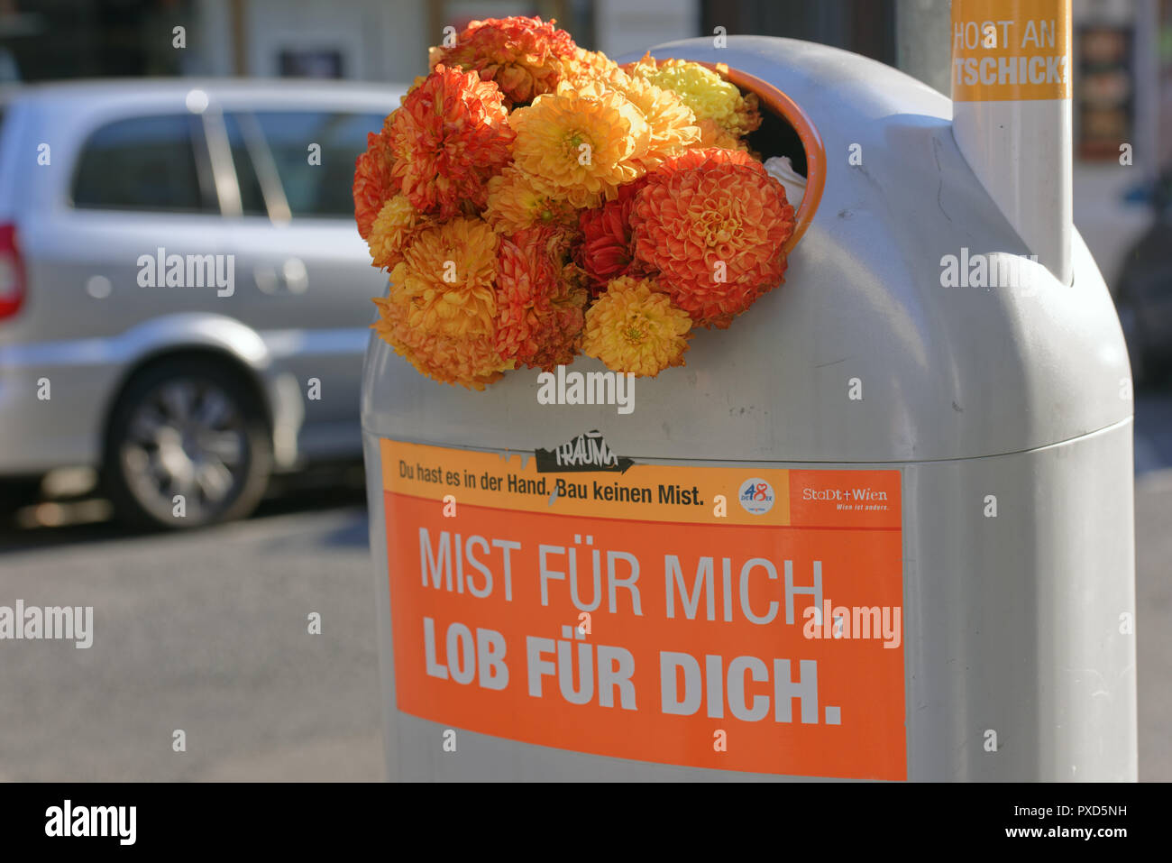 Vienna, Austria - September 18, 2018: Flowers in a trash can on a street of Vienna. The label on a can says: garbage for me, praise to you - Stock Image