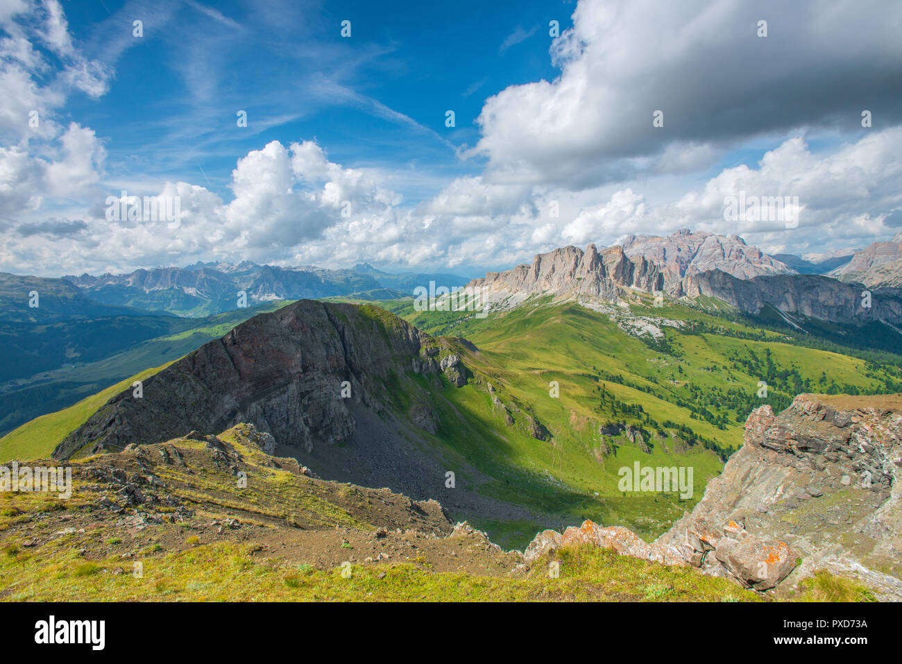 Beautiful view of Italian Dolomites mountainside in the summer. Sharp ridge, mountain wall, forested valleys and grassy pasture. Summit viewpoint. - Stock Image