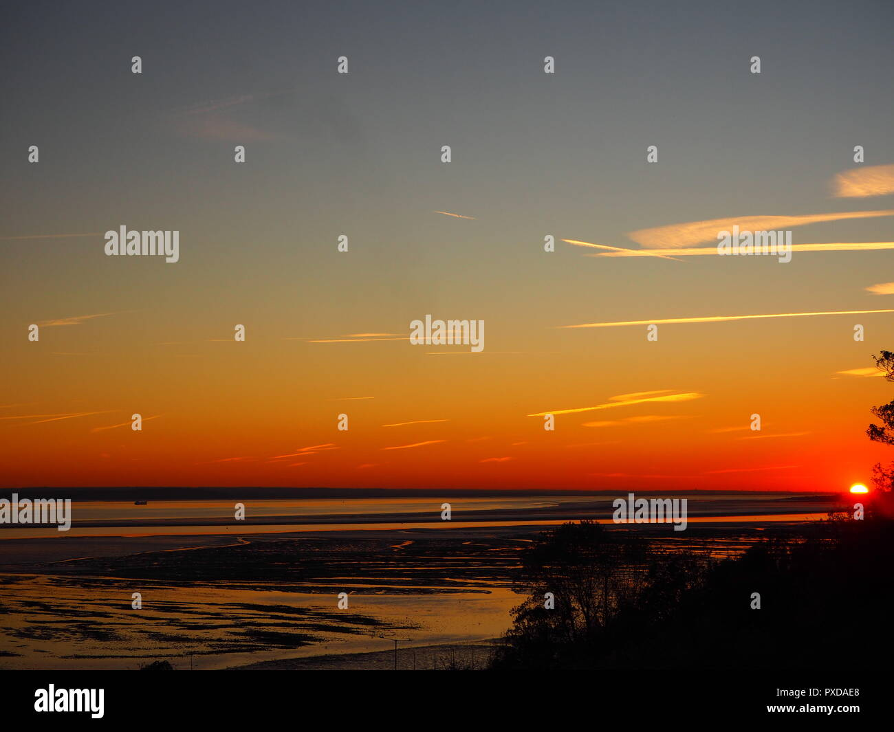 View of the setting sun over the Thames Estuary taken from the cliffs at Southend on sea, Essex, UK - Stock Image