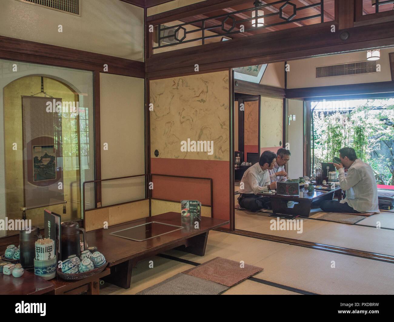 3 Three men eating meal, sitting cross legged at low table,  tatami floor, restaurant Udon Yamadaya, Takamatsu, Kagawa, Japan Stock Photo