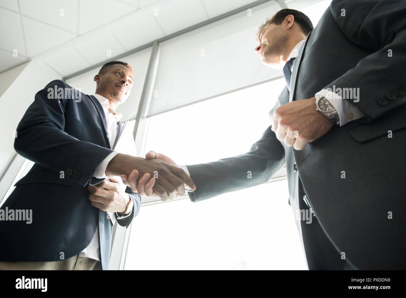 Purposeful African investor making handshake with business compa Stock Photo