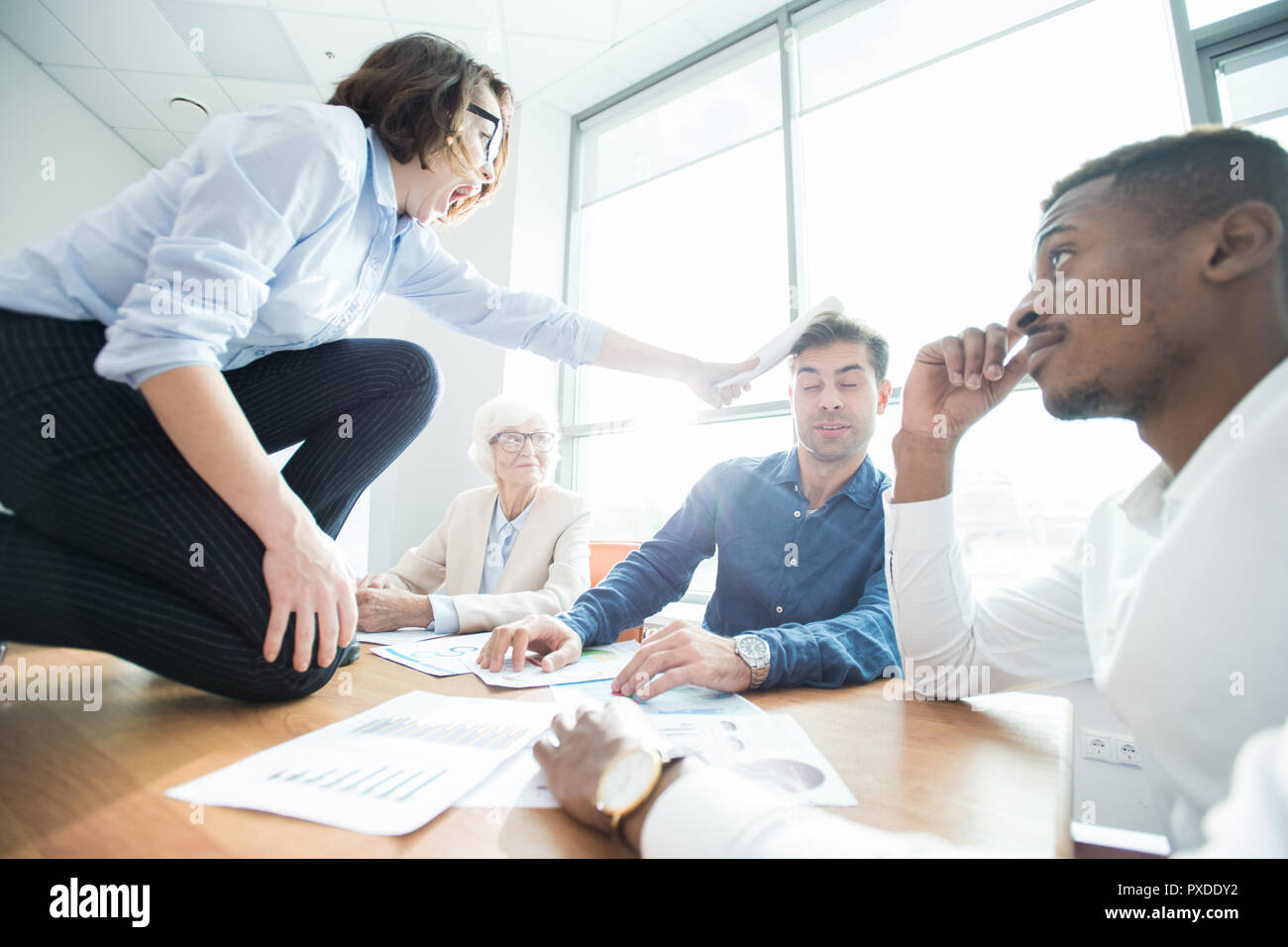 Furious employee hitting boss with rolled paper - Stock Image