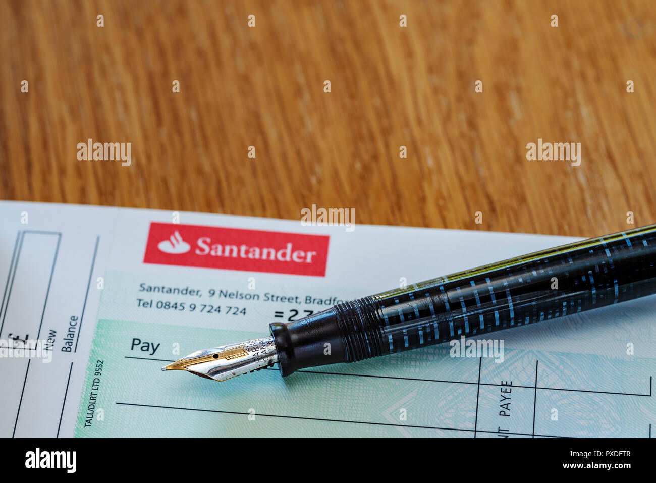 Santander cheque book and fountain pen. Retro or old school banking. Writing a check. - Stock Image