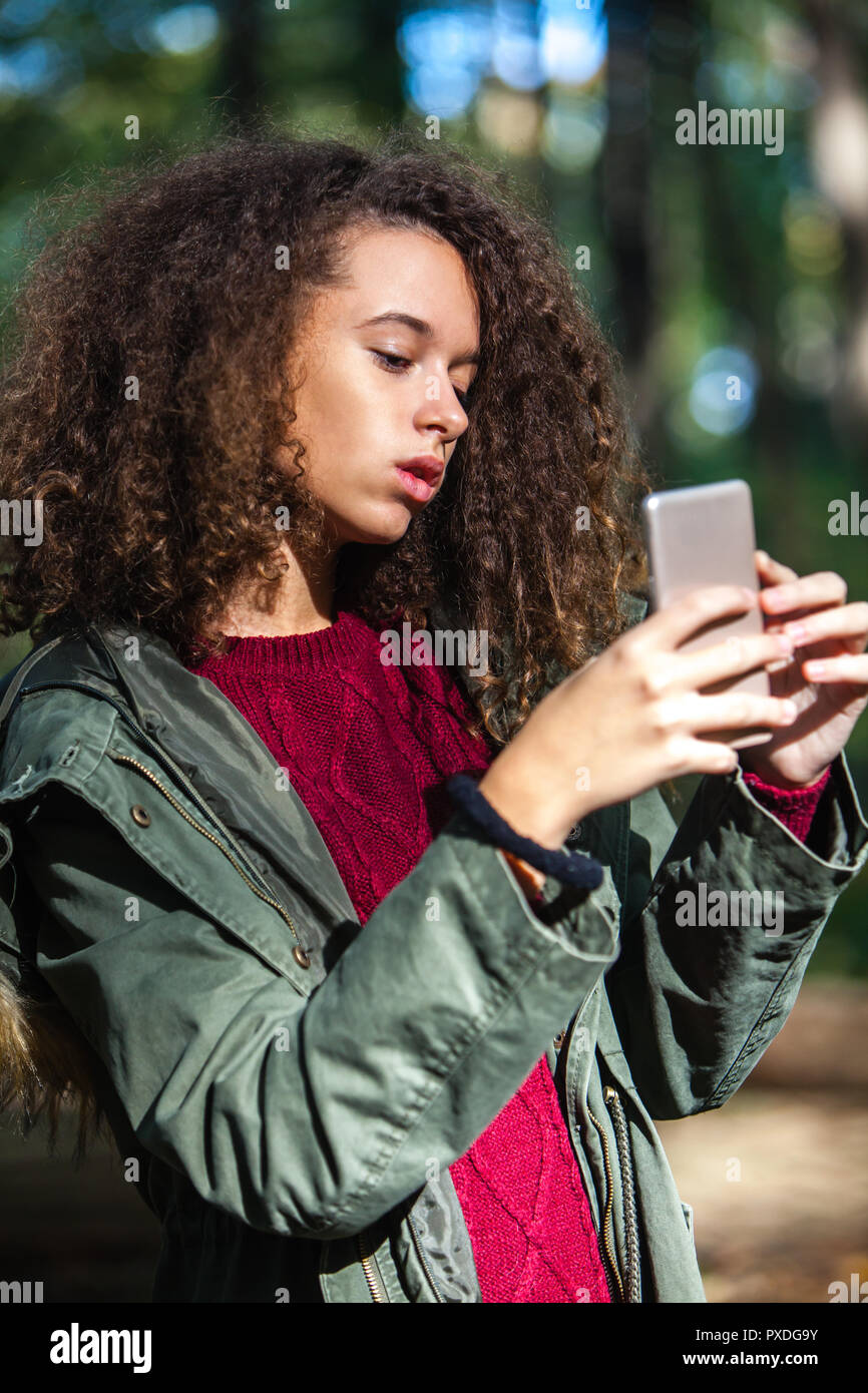 Portrait of the cute curly hair teen girl with smartphone in ...