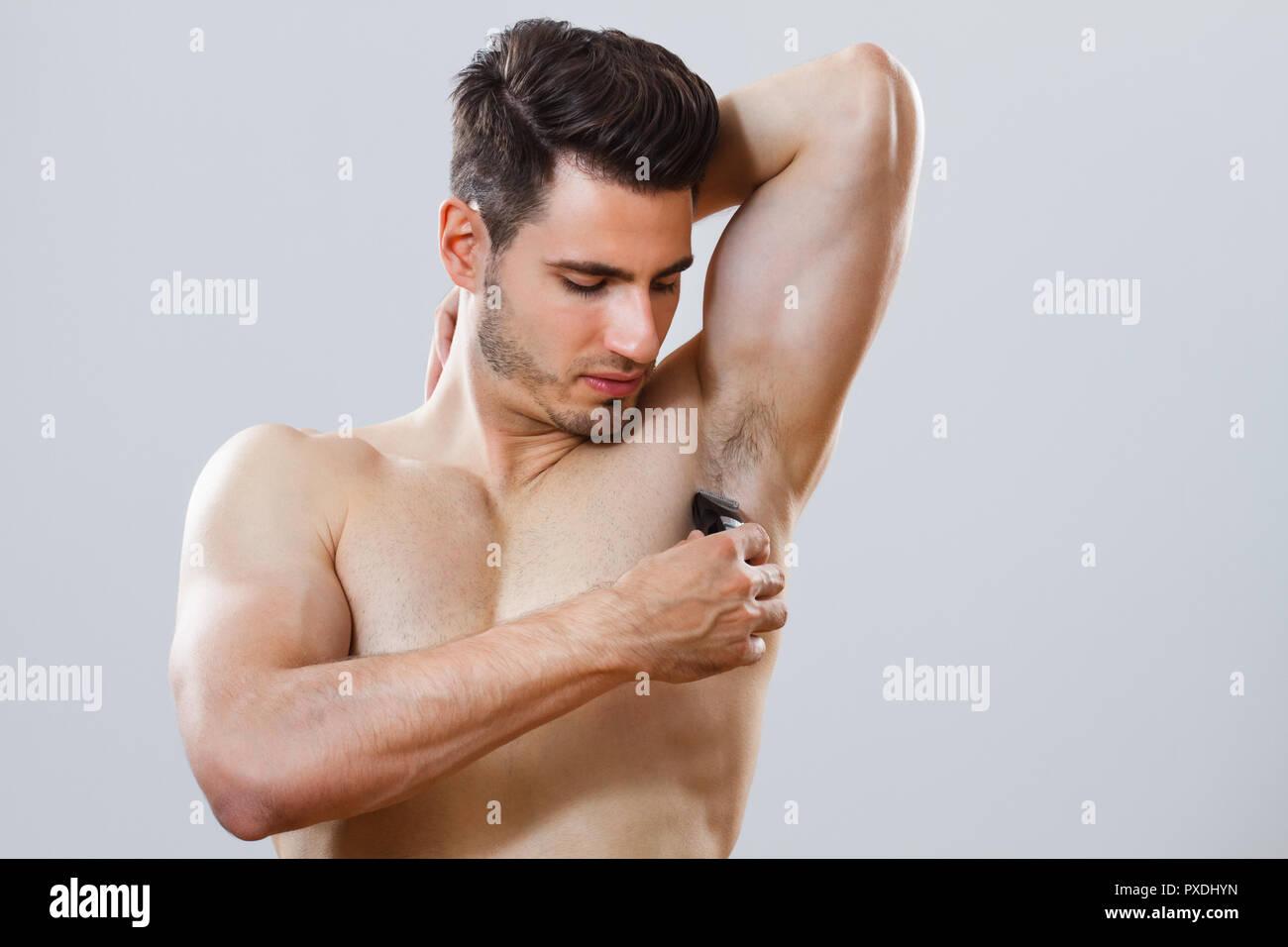 Man shaving his armpit - Stock Image