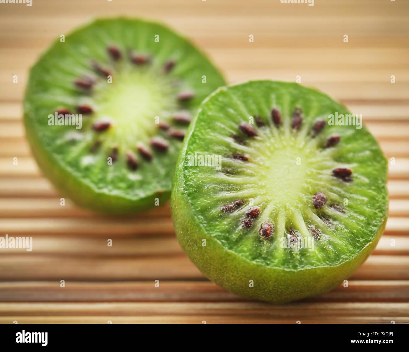 Baby kiwi or Kiwi berry on natural surface - Stock Image