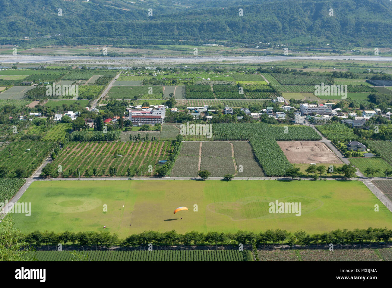 Paraglider landing on field, circle and heart shape on green grass field,countryside aerial view, at Luye Township, Taitung County, Taiwan Stock Photo