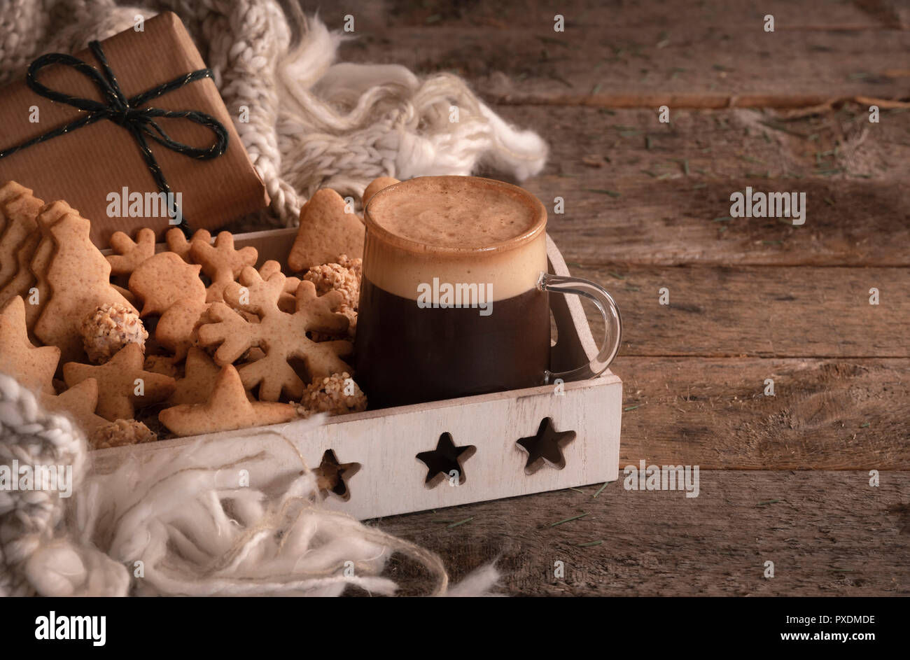 Christmas breakfast table with a tray full of gingerbread cookies, a cup of coffee, a wool scarf, and a gift, on a vintage wooden table. - Stock Image