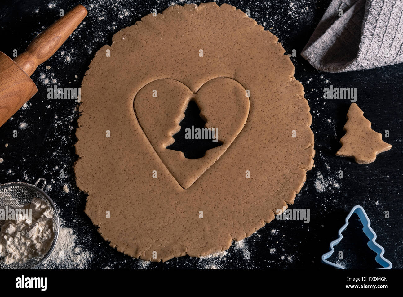 Above view with christmas baking table, gingerbread dough with a heart and tree shape cut from it - Stock Image
