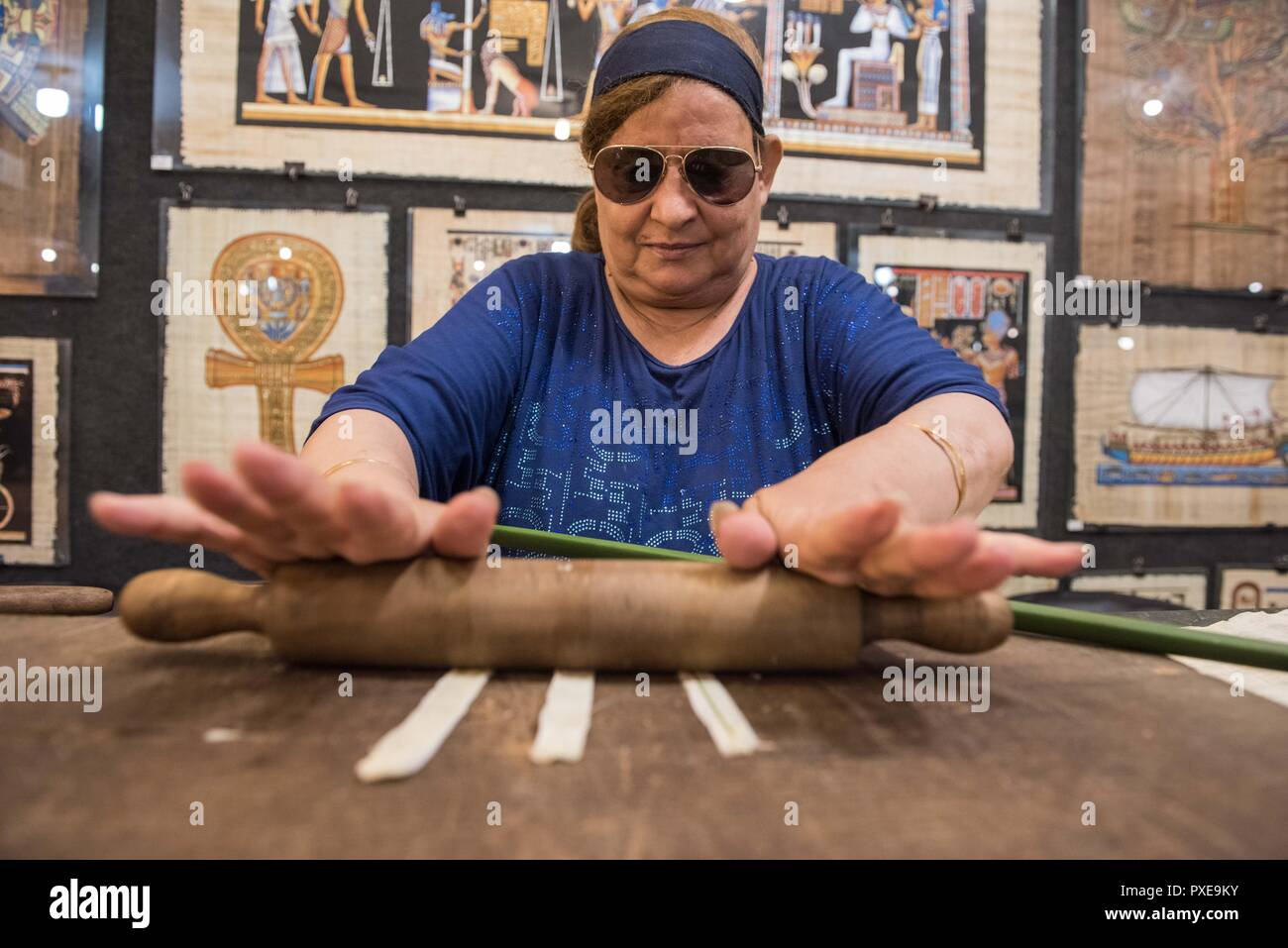 Giza, Egypt. 20th Oct, 2018. A shop assistant squeezes the stems of papyrus plant during a demonstration of making papyrus at a souvenir shop in Giza, Egypt, on Oct. 20, 2018. Made from papyrus plant stems, the papyrus was used for writing and drawing on by ancient Egyptians thousands years ago. Nowadays, with the ancient Egyptian writings and Pharaonic drawings, papyrus has always been an interesting souvenir bought by tourists in Egypt. Credit: Meng Tao/Xinhua/Alamy Live News - Stock Image
