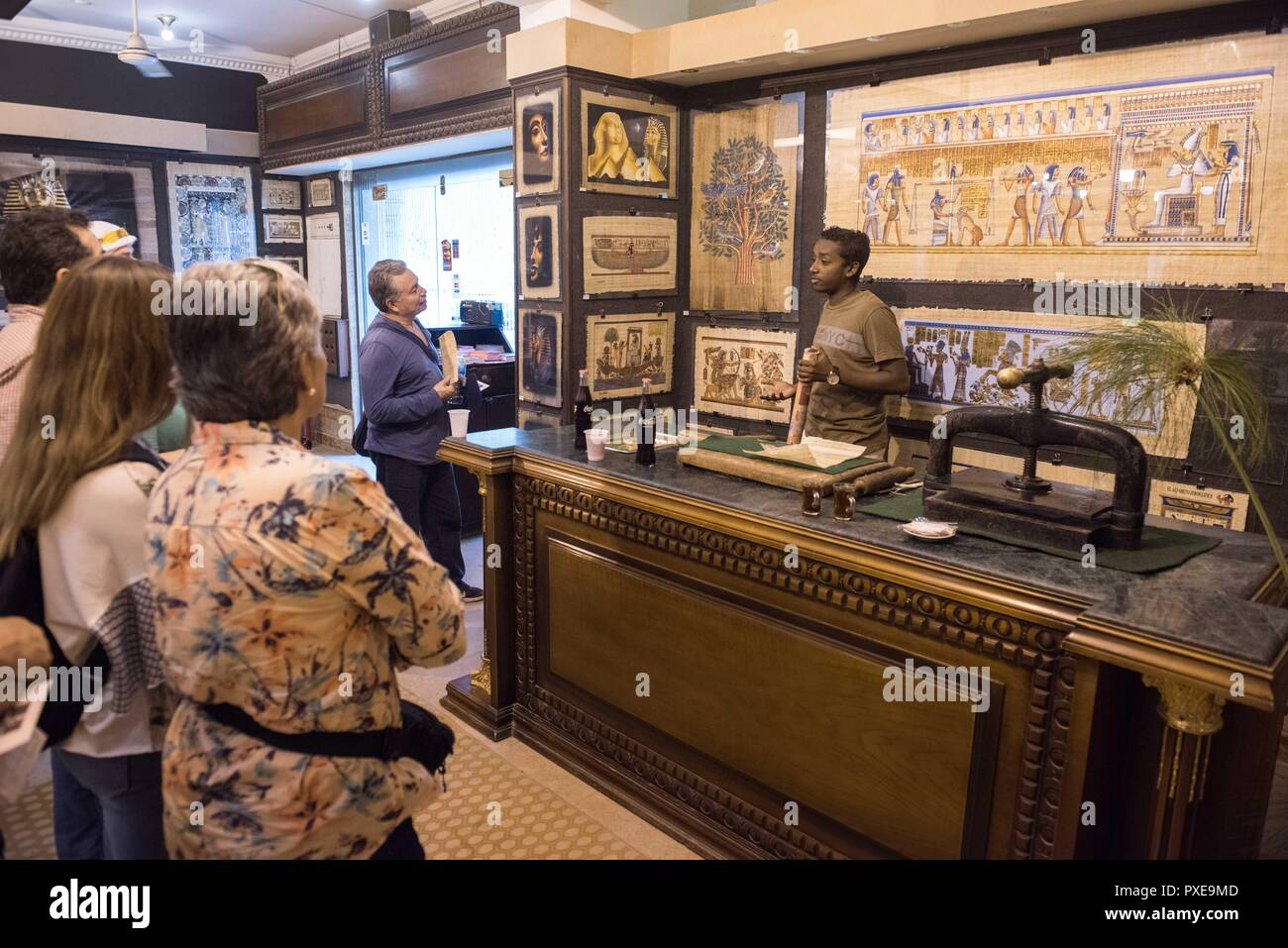 Giza, Egypt. 20th Oct, 2018. A shop assistant introduces the papyrus to tourists at a souvenir shop in Giza, Egypt, on Oct. 20, 2018. Made from papyrus plant stems, the papyrus was used for writing and drawing on by ancient Egyptians thousands years ago. Nowadays, with the ancient Egyptian writings and Pharaonic drawings, papyrus has always been an interesting souvenir bought by tourists in Egypt. Credit: Meng Tao/Xinhua/Alamy Live News - Stock Image