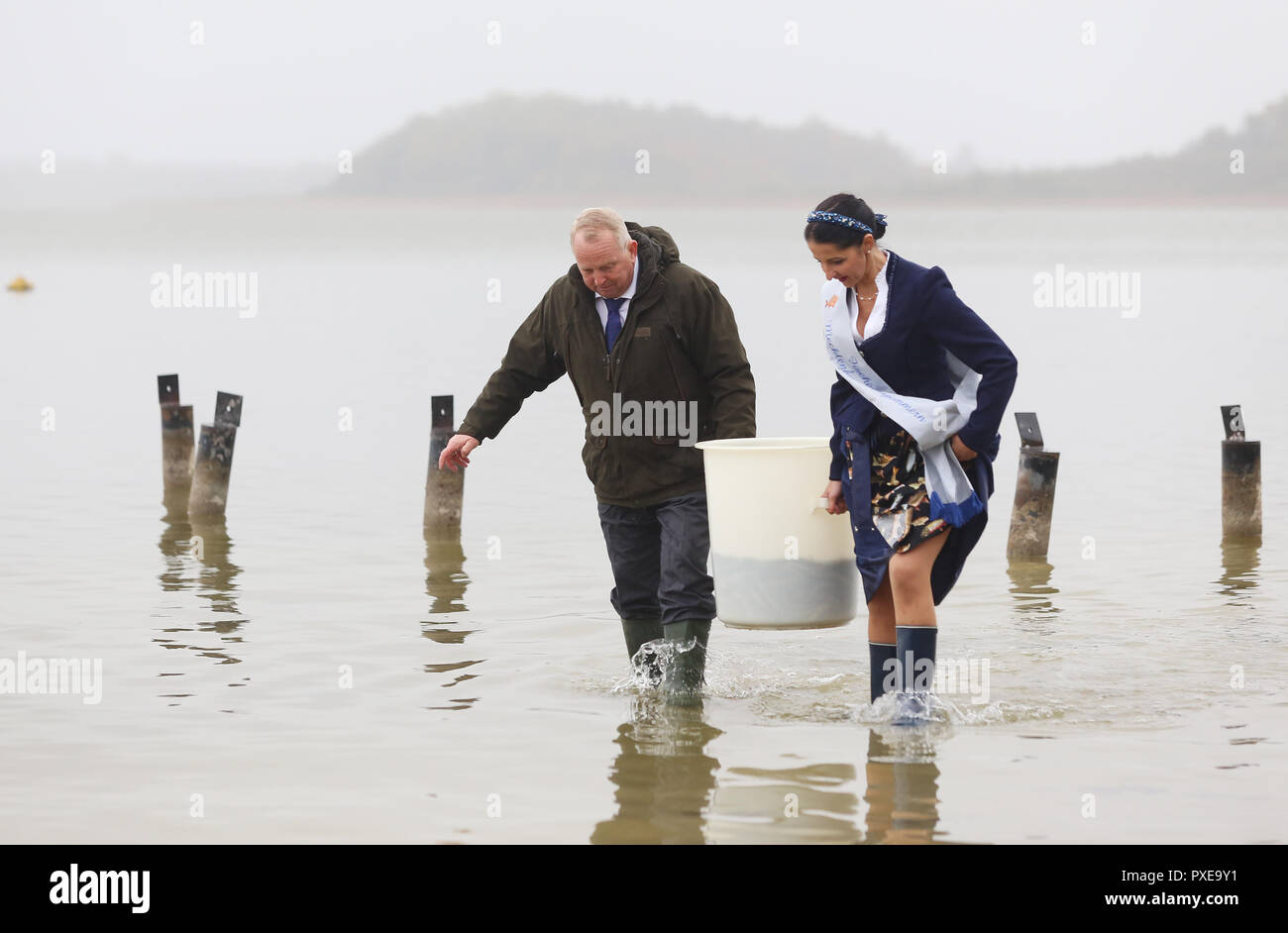 """22 October 2018, Mecklenburg-Western Pomerania, Goldberg: Till Backhaus (SPD), Agriculture Minister of Mecklenburg-Western Pomerania, and Jeannette Dehmel, 1st Fisher Queen of Mecklenburg-Western Pomerania, are releasing pre-stretched (fed) young eels in Lake Goldberg. For 25 years, the """"Landesanglerverband MV"""" has occupied eels worth around 100,000 euros annually. The campaign """"Save the European Eel"""" should contribute to the conservation of eels in Mecklenburg-Vorpommern. Photo: Danny Gohlke/dpa-Zentralbild/dpa Stock Photo"""