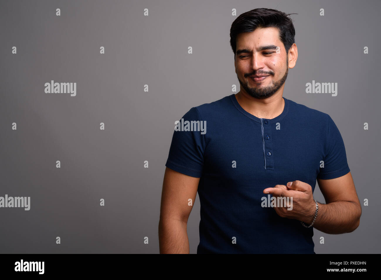 Young handsome bearded Persian man against gray background - Stock Image