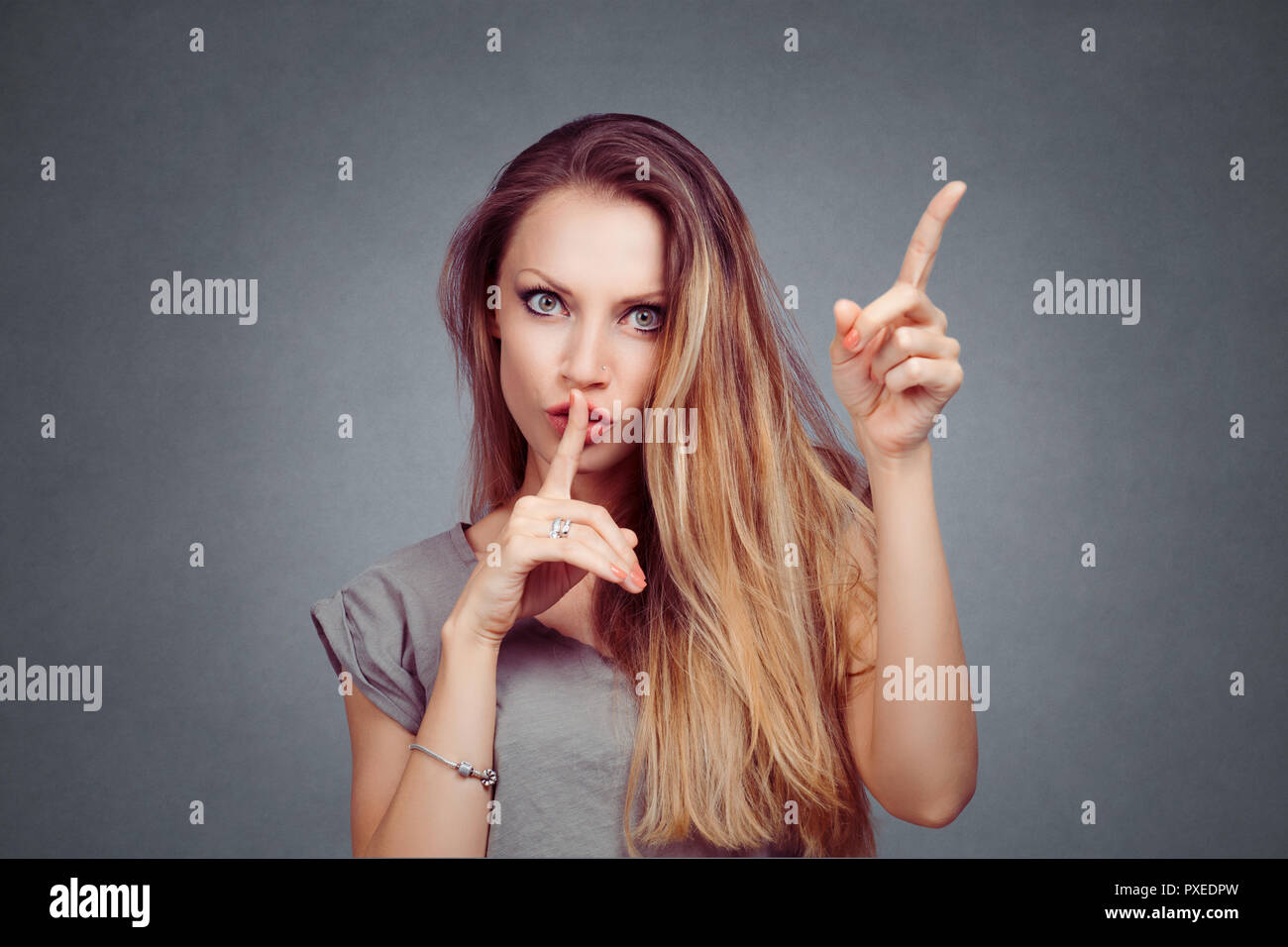 SHH. Angry woman showing shh, silence, hush sign gesture with one hand, attention listen to me with other hand isolated on gray grey studio wall Backg - Stock Image