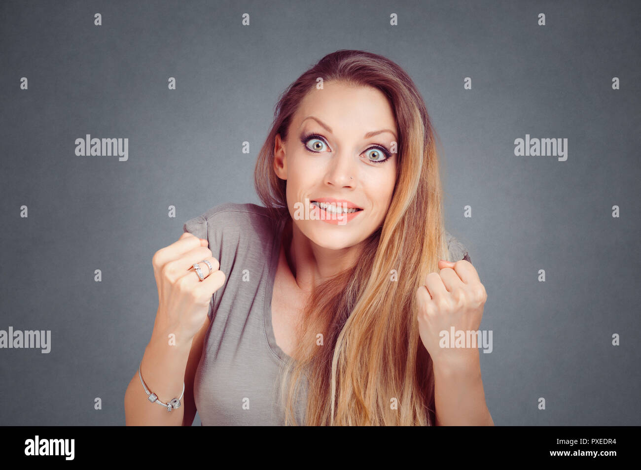 woman stunned pumping fists hands clenched in expectation about to win a lottery or something isolated on gray studio wall Background with copy space. - Stock Image