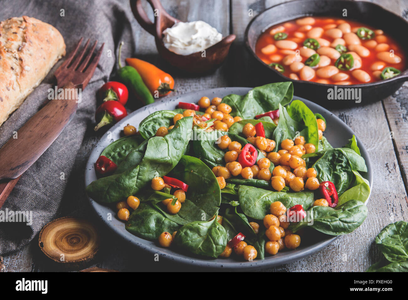 Chickpeas and veggies salad with spinach leaves, healthy homemade vegan food, diet. white beans in tomato sauce - Stock Image