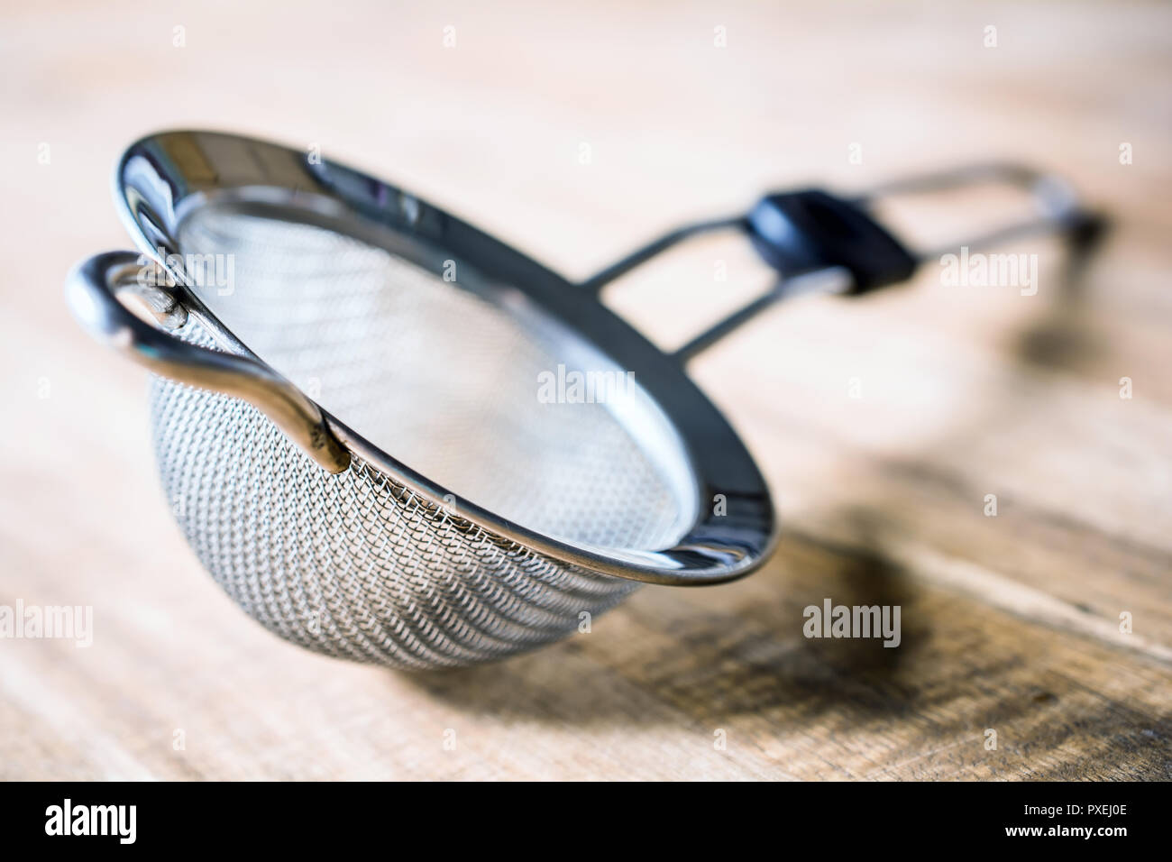 A Stainless Sieve Lying Down On A Wooden Table - Stock Image