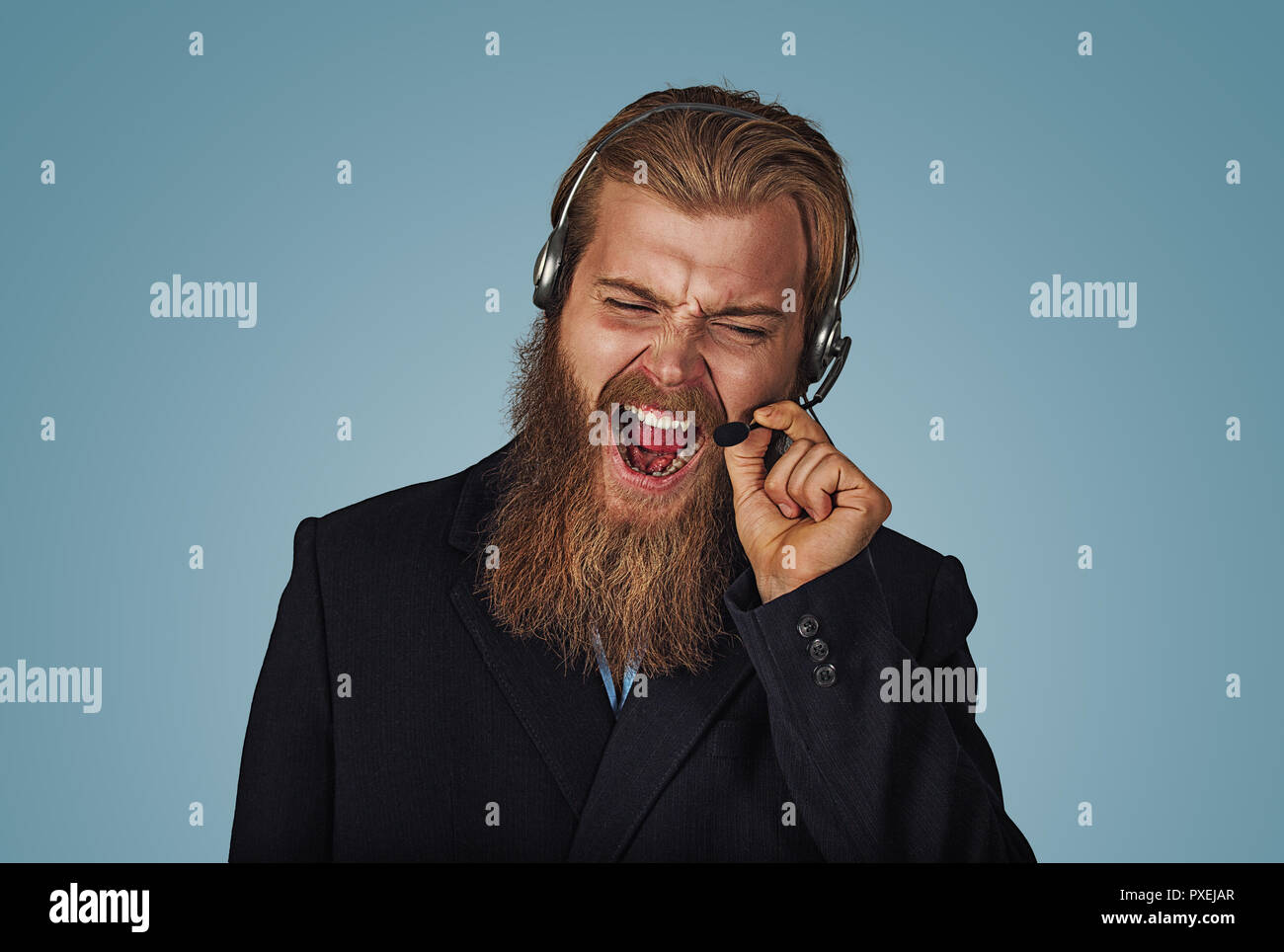 Angry Bearded hipster businessman aggressive customer support phone operator with headset, he is yelling and having a discussion with a customer isola - Stock Image